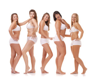A group of women with different body shapes standing together in their underwear while isolated on white