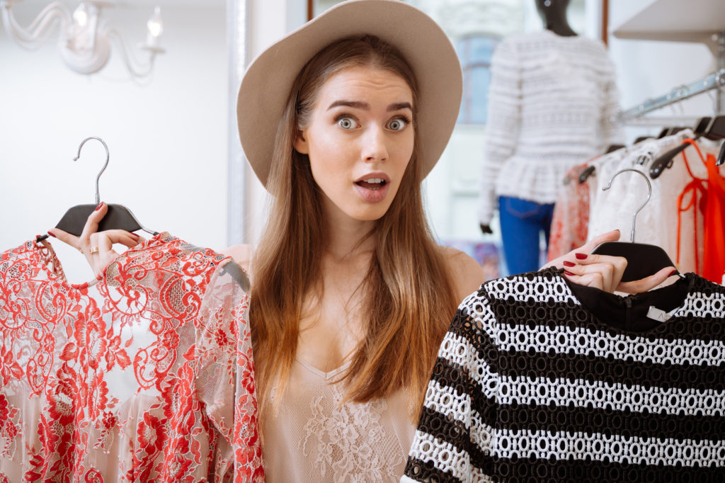 Image of confused woman choosing between two dresses